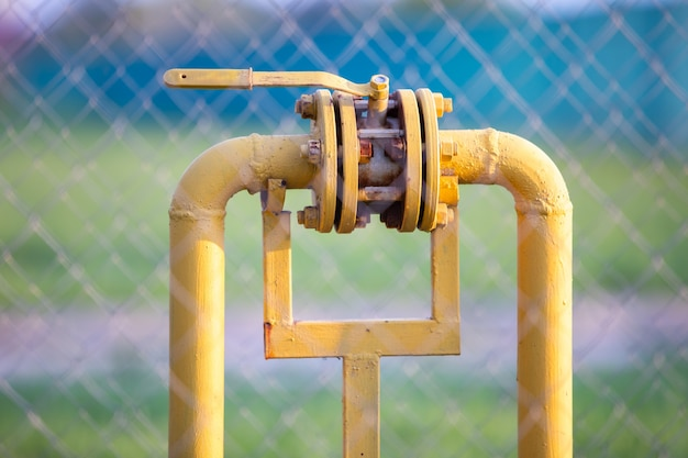 Zawór gazowy na żółtej metalowej rurce.