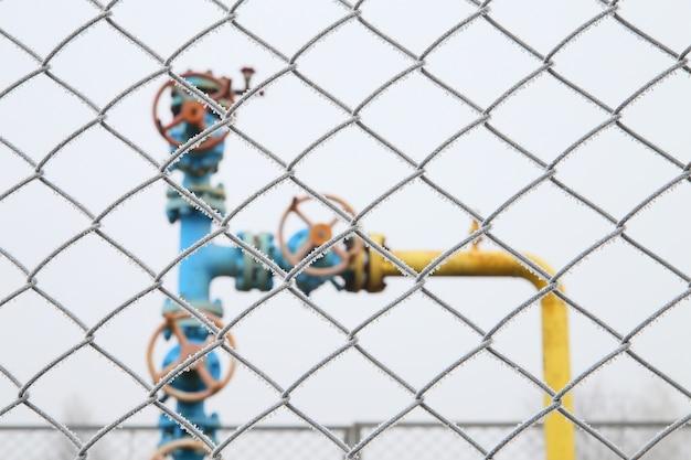 Zawór gazowy z ogrodzeniem na pierwszym planie.
