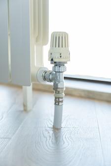 Zawór termostatu na białym grzejniku z bliska