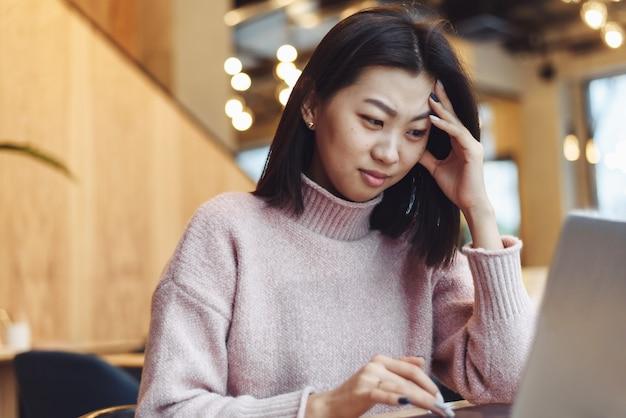 Zawstydzona dziewczyna pracuje na laptopie w kawiarni i jest niezadowolona z błędów