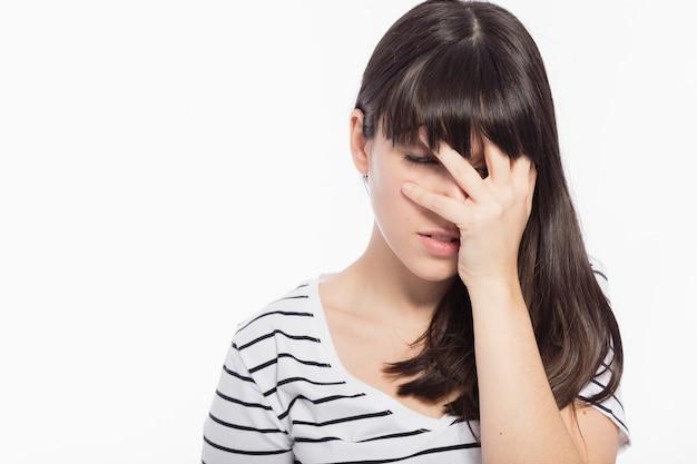 Zawstydzona kobieta zakrywająca twarz