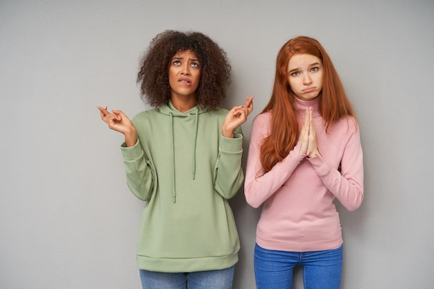 Zawstydzona młoda, dość kręcona ciemnoskóra brunetka dama trzyma palce na szczęście, patrząc w górę z rozpaczliwą twarzą i gryzącą dolną wargą, pozując na szarej ścianie ze swoim przyjacielem