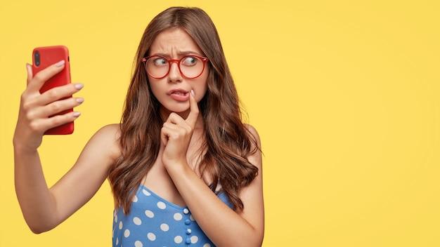 Zawstydzona młoda europejka z nerwowym zmartwieniem na twarzy, nosi okulary, trzyma z przodu nowoczesny smartfon