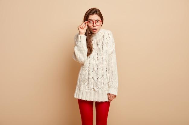 Zawstydzona młoda modelka trzyma rękę na krawędzi okularów, ma zdziwiony wyraz twarzy, zaskoczony, że zauważa coś niesamowitego i niewiarygodnego, nosi zimowy sweter, odizolowany na beżowej ścianie