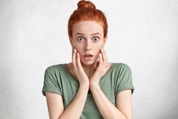 Zawstydzona rudowłosa zszokowana kobieta patrzy na aparat z wytrzeszczonymi oczami, ubrana w zwykły strój, nie może uwierzyć w tragedię, strach przed czymś.