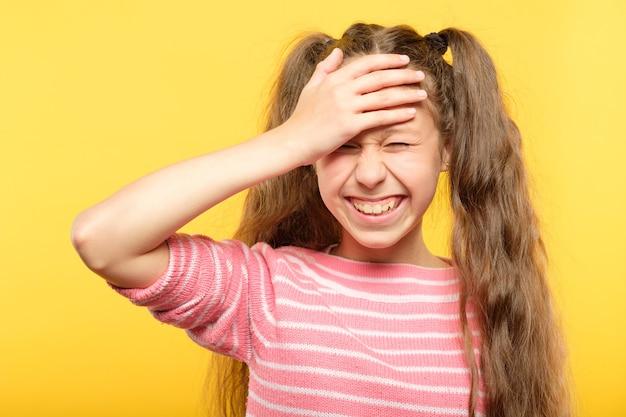 Zawstydzona uśmiechnięta dziewczyna zakrywająca dłonią czoło. wstyd i wstyd.
