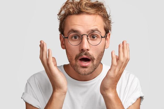 Zawstydzony atrakcyjny młody mężczyzna trzyma ręce blisko głowy, lekko otwiera usta, zaskoczony tym, co widzi, ma rude wąsy, ubrany niedbale