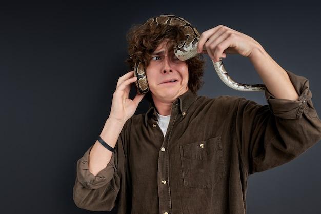 Zawstydzony facet próbujący bawić się wężem, przestraszony przez niego. portret. koncepcja ludzi i zwierząt