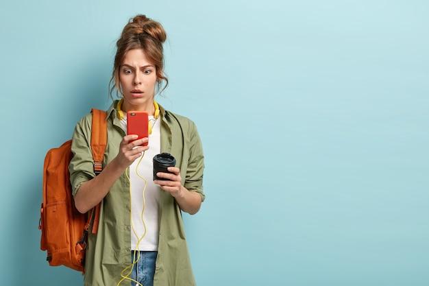 Zawstydzony młody student z uczesanymi włosami, nosi zwykłą koszulę, zaskoczony złym połączeniem internetowym, wpatruje się w ekran telefonu komórkowego, pobiera muzykę z listy odtwarzania, pije kawę na wynos