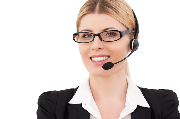 Zawsze gotowy do pomocy. pewny siebie dojrzały przedstawiciel obsługi klienta w zestawie słuchawkowym, patrzący na kamerę i uśmiechający się, stojąc na białym tle