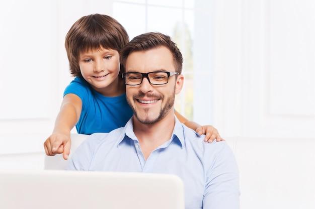Zawsze gotowy pomóc mojemu ojcu. szczęśliwy ojciec i syn surfują po sieci w domu, podczas gdy mały chłopiec wskazuje monitor laptopa i uśmiecha się