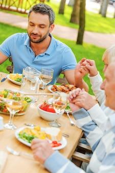 Zawsze jest coś, za co można być wdzięcznym. rodzina trzymająca się za ręce i modląca się przed obiadem, siedząc przy stole na świeżym powietrzu