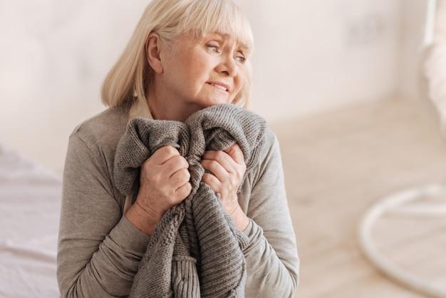 Zawsze jesteś w moim sercu. pogodna starsza kobieta przyciska do serca sweter z dzianiny i myśli o swoim mężu w depresji