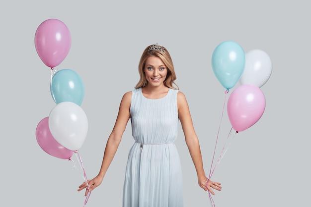 Zawsze młody duchem. atrakcyjna młoda kobieta trzymająca balony i patrząca na kamerę z uśmiechem, stojąc na szarym tle
