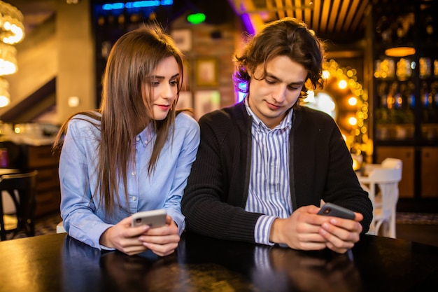 Zawsze połączony, uzależniony od internetu, młoda para w kawiarni patrząc na swoje smartfony