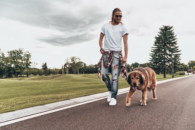 Zawsze razem. pełna długość przystojnego młodego mężczyzny spacerującego z psem podczas spędzania czasu na świeżym powietrzu