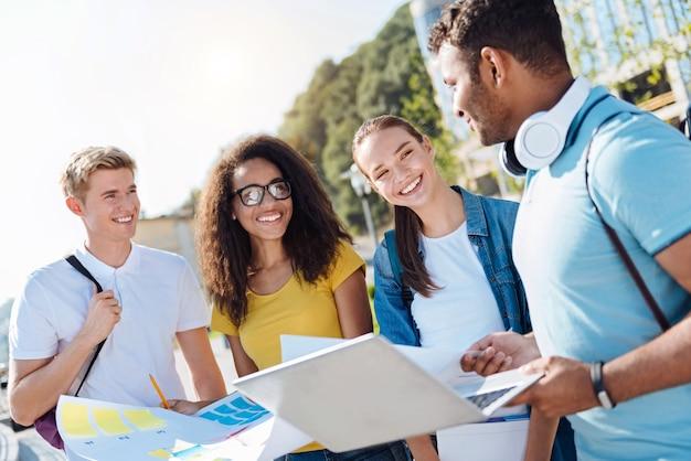 Zawsze się uśmiechaj. zachwyceni młodzi ludzie z uśmiechem na twarzy i trzymający papiery, patrząc na przyjaciela