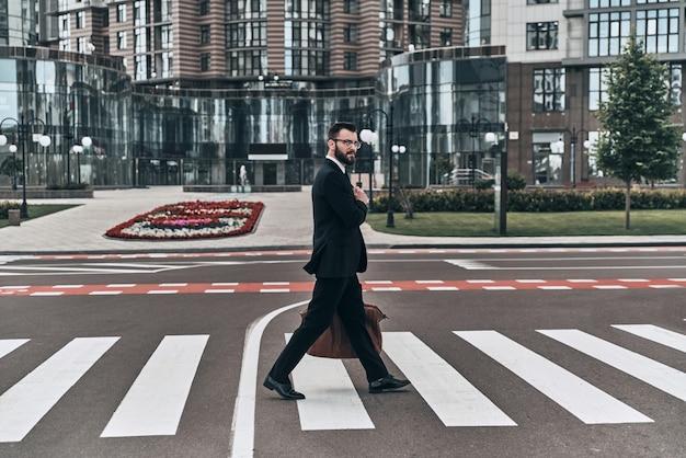Zawsze uważaj. pełna długość młodego mężczyzny w pełnym garniturze przechodzącego przez ulicę