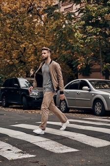Zawsze uważaj. pełna długość przystojnego młodego mężczyzny w stroju codziennym, przechodzącego przez przejście dla pieszych, spędzając czas na świeżym powietrzu