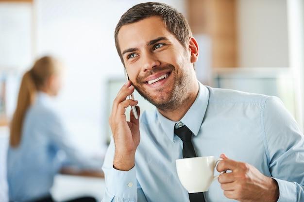 Zawsze w dobrym nastroju. wesoły młody biznesmen w stroju formalnym rozmawia przez telefon komórkowy i trzyma filiżankę kawy, podczas gdy jego koleżanka pracuje w tle