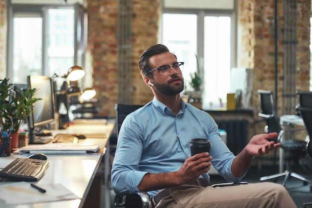 Zawsze w kontakcie portret młodego brodatego mężczyzny w okularach i słuchawkach rozmawiającego z klientem