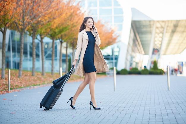 Zawsze w ruchu. kobieta spaceru na lotnisku i rozmawiać na telefon komórkowy