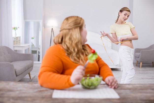 Zazdrość. blond kobieta z nadwagą je sałatkę i patrzy na swojego szczupłego przyjaciela