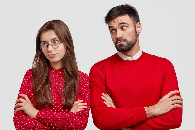 Zazdrosna dziewczyna odwraca się od chłopaka, czuje się urażona po rozwiązaniu związku, trzyma ręce skrzyżowane