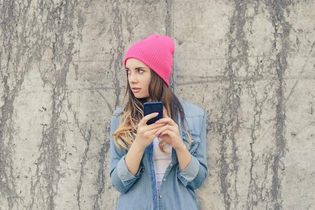 Zazdrosna kobieta sprawdza telefon komórkowy swojego chłopaka. kobieta czyta tajne sms na swoim telefonie komórkowym. ubrana jest w zwykłe ubranie, różowy kapelusz. zdjęcie z bliska, szare kamienne tło