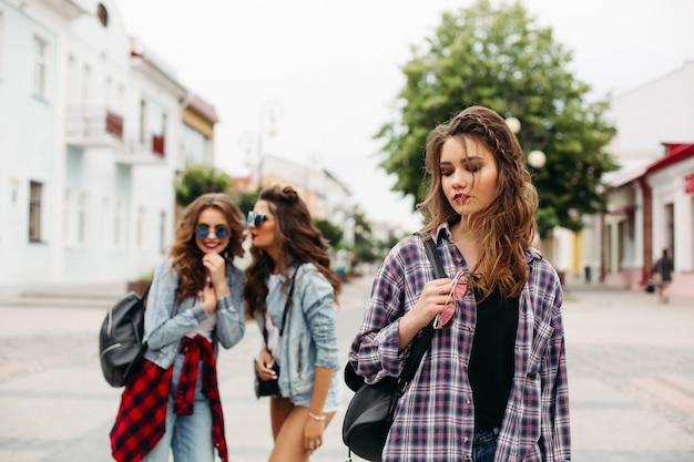 Zazdrosne dziewczyny szepczą o trzeciej dziewczynie przed kamerą.