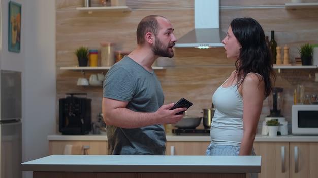 Zazdrosny mąż prosi o wyjaśnienia po sprawdzeniu telefonu żony. oszukany, zły, sfrustrowany, zirytowany mężczyzna oskarżający kobietę o niewierność, argumentując ją wiadomościami na smartfonie, krzycząc zdesperowany