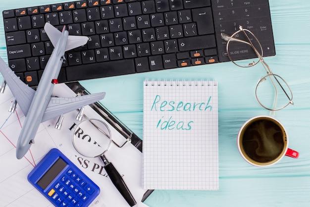 Zbadaj pomysły dotyczące notatnika z materiałami biurowymi. filiżanka kawy kalkulator samolot klawiatura na turkusowym tle.