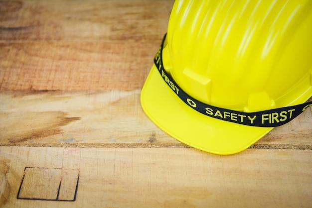 Zbawczego pierwszy pojęcia odzieży hełma żółtego ciężkiego bezpieczeństwa kapelusz - konstruuje pracownika hełm na drewnianym tle