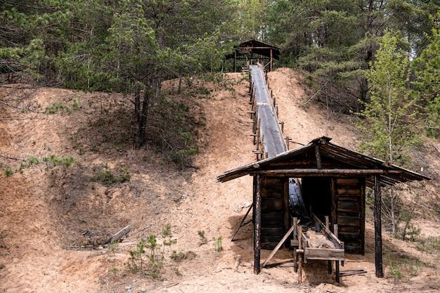 Zbieg drewniany z dobudówką wzdłuż piaszczystego zjazdu w lesie