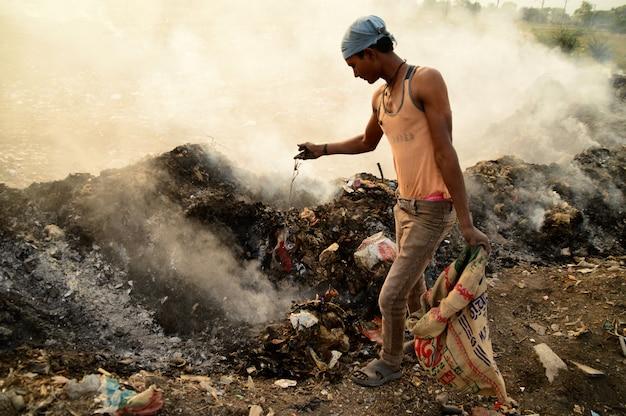 Zbieracze szmat szukają materiałów nadających się do recyklingu w śmietnikach i zanieczyszczeniu powietrza w indiach