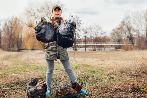 Zbieranie śmieci. kobieta wolontariusz sprzątanie śmieci w parku. zbieranie śmieci na zewnątrz. ekologia i środowisko