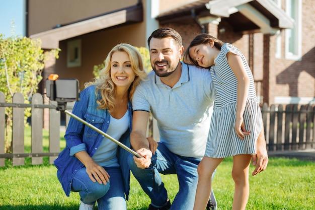 Zbieranie wspomnień. uroczy młody mężczyzna kucający na trawniku między żoną i córką i robiąc selfie swojej rodziny kijem do selfie