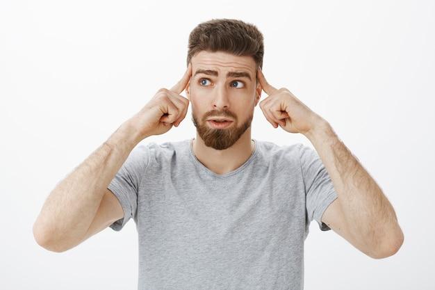 Zbierz się i pomyśl. portret niepewnego, zamyślonego, zmartwionego przystojnego mężczyzny z brodą i wąsami, dotykającego skroni palcami, patrzącego w lewy górny róg zatroskany podczas myślenia