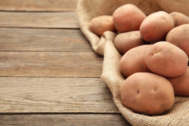 Zbierz ziemniaki w jutowym worku na rustykalnym tle z miejsca na kopię