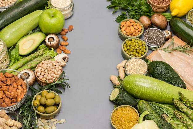 Zbilansowany zestaw żywności, zielone warzywa, nasiona orzechów, mięso z kurczaka na szarym tle