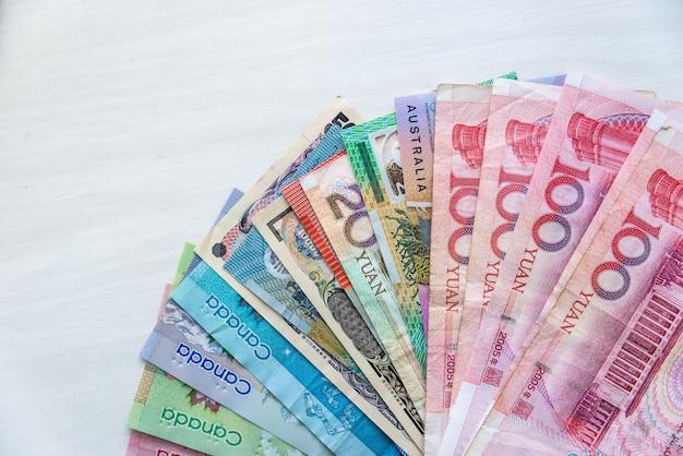 Zbiór banknotów czterech krajów na drewnianym stole