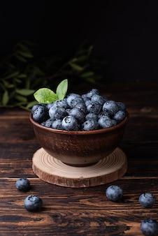 Zbiór letnich jagód, dojrzałe jagody z kroplami wody w misce na ciemnym tle drewnianych, zdrowa żywność.