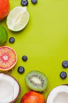 Zbiór owoców tropikalnych kiwi, krwista pomarańcza, kokos, jagoda, limonka, na zielonym tle. owocowa rama owocowa. flatlay z copyspace. koncepcja odporności. owoce dla wzmocnienia odporności. jedzenie pop-artu