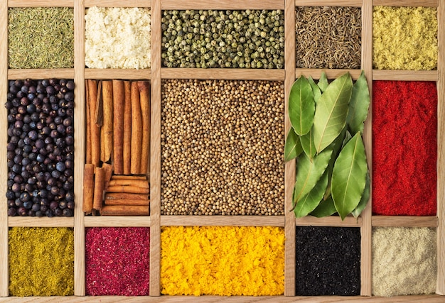 Zbiór przypraw w drewnianym pudełku, widok z góry. indyjskie przyprawy jako ścianka do pakowania z jedzeniem.