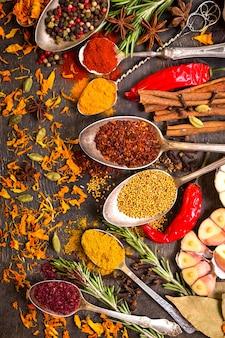 Zbiór różnych aromatycznych kolorowych przypraw w stare zabytkowe łyżki i zioła na ciemnym tle drewniane.