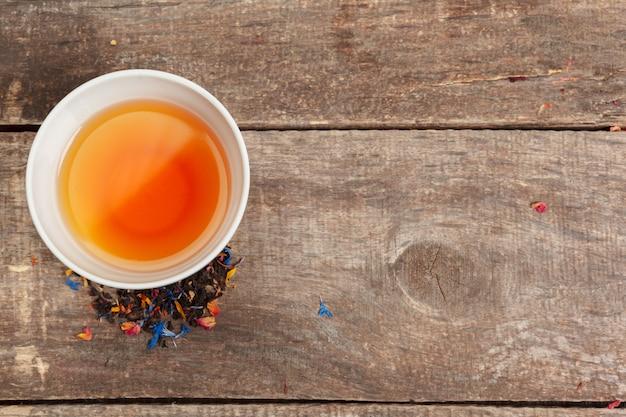 Zbiór różnych herbat w filiżankach z liśćmi herbaty