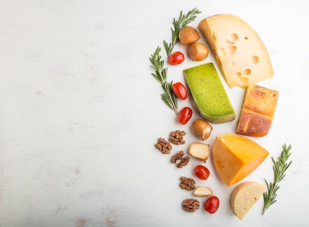 Zbiór różnych rodzajów sera z rozmarynem i pomidorami na białej drewnianej powierzchni