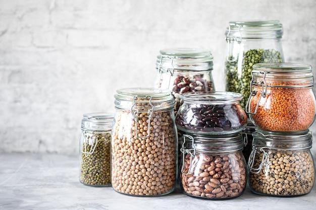 Zbiór różnych roślin strączkowych w szklanych słoikach, betonowy biały stół. źródło białka dla wegetarian. pojęcie zdrowego odżywiania i przechowywania żywności.