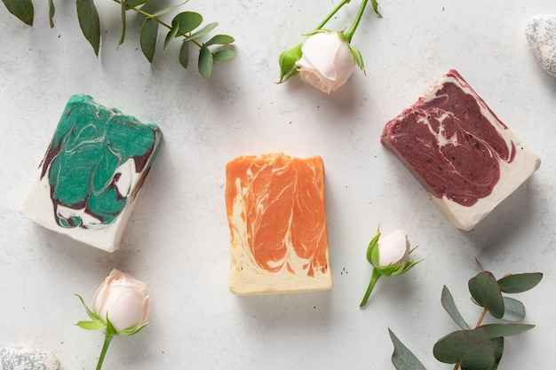 Zbiór różnych ziołowych kostek mydła na białym tle z kwiatami i eukaliptusem. kosmetyki organiczne, koncepcja spa. leżał płasko
