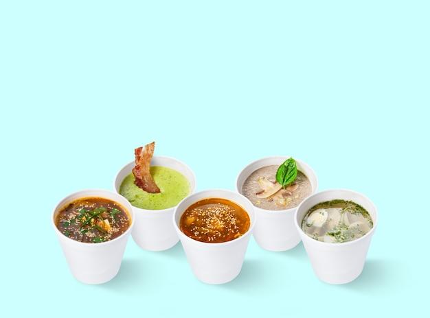 Zbiór różnych zup w restauracji na niebieskim tle